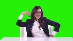 Retrato de una mujer en la oficina en un fondo verde Sonrisas morenas y danzas almacen de video