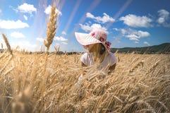 Retrato de una mujer en un fondo del campo de trigo Imagen de archivo libre de regalías