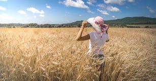 Retrato de una mujer en un fondo del campo de trigo Imágenes de archivo libres de regalías