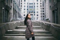 Retrato de una mujer en un tema del negocio La muchacha morena caucásica joven en la chaqueta larga, capa con el bolso de cuero n imagen de archivo libre de regalías