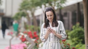 Retrato de una mujer en un vestido largo que manda un SMS en smartphone en la ciudad almacen de metraje de vídeo