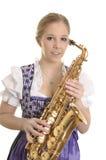 Retrato de una mujer en vestido del dirndl con el saxofón Foto de archivo libre de regalías
