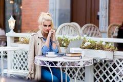 Retrato de una mujer encantadora joven que presenta mientras que se sienta en la tabla con el red-libro portátil abierto, Fotos de archivo