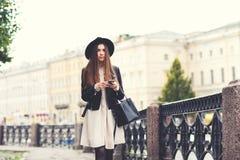 Retrato de una mujer enrrollada atractiva joven con el pelo largo que charla en su teléfono móvil mientras que paseo en la calle Imágenes de archivo libres de regalías