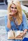 Retrato de una mujer feliz alegre que presenta mientras que se sienta con el libro en café al aire libre durante tiempo de la rec Imagen de archivo