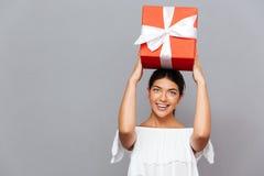 Retrato de una mujer feliz con la caja de regalo en la cabeza Foto de archivo