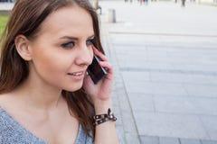 Retrato de una mujer feliz de la moda con el teléfono móvil En un backgr Foto de archivo