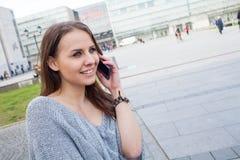 Retrato de una mujer feliz de la moda con el teléfono móvil En un backgr Fotos de archivo libres de regalías