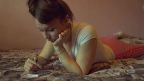 Retrato de una mujer feliz en su mandar un SMS precioso del dormitorio almacen de video