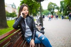 Retrato de una mujer feliz que se sienta en el banco y que habla en el teléfono al aire libre Imagenes de archivo