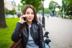 Retrato de una mujer feliz que se sienta en el banco y que habla en el teléfono al aire libre Fotografía de archivo libre de regalías
