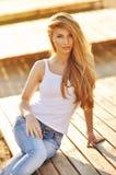 Retrato de una mujer hermosa con el pelo magnífico en un top blanco y vaqueros elegantes Fotos de archivo