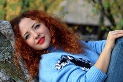 Retrato de una mujer hermosa con el pelo rojo y una sonrisa hermosa que miente en una manta, extensión hacia fuera en un árbol So fotos de archivo libres de regalías