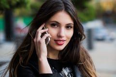 Retrato de una mujer hermosa con sonrisa blanca perfecta que habla en el teléfono móvil al aire libre Imagen de archivo