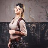 Retrato de una mujer hermosa del steampunk en vidrios del aviador sobre fondo gris fotos de archivo