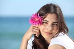 Retrato de una mujer hermosa en la playa con una flor rosada Fotos de archivo libres de regalías