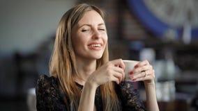 Retrato de una mujer hermosa en un café o un restaurante Una muchacha bebe té o café y los sueños sobre algo almacen de video