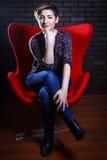 Retrato de una mujer hermosa en una butaca roja Foto de archivo libre de regalías