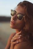 Retrato de una mujer hermosa joven con el pelo rizado largo en gafas de sol Fotos de archivo
