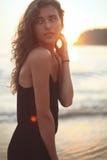 Retrato de una mujer hermosa joven con el pelo rizado largo en la playa Foto de archivo libre de regalías