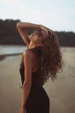 Retrato de una mujer hermosa joven con el pelo rizado largo en la playa Foto de archivo