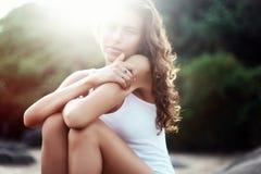 Retrato de una mujer hermosa joven con el pelo rizado largo en la playa Fotografía de archivo libre de regalías