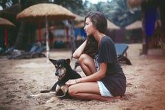 Retrato de una mujer hermosa joven con el pelo rizado y el perro largos Imágenes de archivo libres de regalías