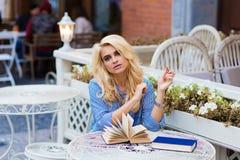 Retrato de una mujer hermosa joven con el pelo rubio de lujo que se sienta con los libros en café de la acera en día de primavera Foto de archivo