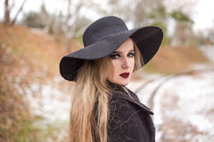 Retrato de una mujer hermosa joven en estilo retro del sombrero negro Fotos de archivo libres de regalías