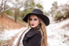 Retrato de una mujer hermosa joven en estilo retro del sombrero negro Imágenes de archivo libres de regalías