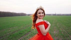 Retrato de una mujer hermosa joven en un vestido rojo contra un fondo de la naturaleza almacen de video