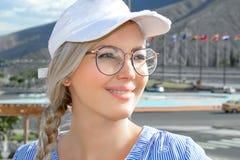 Retrato de una mujer hermosa joven, rubio en un casquillo, vidrios y con una guadaña en el aire abierto imagen de archivo libre de regalías