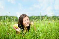 Retrato de una mujer hermosa que come una manzana Imagen de archivo