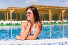 Retrato de una mujer hermosa que presenta por la piscina, día de verano, al aire libre Vocación del verano Imagen de archivo