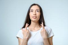 Retrato de una mujer hermosa que ruega con los fingeres cruzados Imagen de archivo