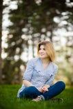 Retrato de una mujer hermosa que se sienta en hierba con una sonrisa Imágenes de archivo libres de regalías