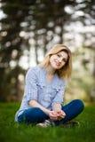 Retrato de una mujer hermosa que se sienta en hierba con una sonrisa Imagenes de archivo