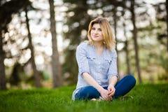 Retrato de una mujer hermosa que se sienta en hierba con una sonrisa Fotos de archivo libres de regalías