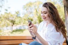 Retrato de una mujer hermosa que usa smartphone en el banco Fotografía de archivo libre de regalías
