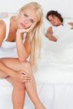Retrato de una mujer infeliz que se sienta en una cama Fotografía de archivo