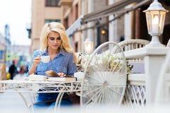 Retrato de una mujer inteligente joven que goza del café durante el libro leído mientras que se sienta en restaurante en el aire  Fotos de archivo