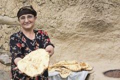 Retrato de una mujer iraní en el paño tradicional que lleva a cabo un cocer Imagen de archivo libre de regalías