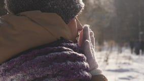 Retrato de una mujer joven al aire libre quién está respirando en sus brazos para mantener caliente mientras que camina el parque almacen de metraje de vídeo
