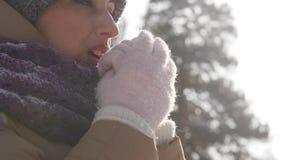 Retrato de una mujer joven al aire libre quién está respirando en sus brazos para mantener caliente mientras que camina el parque almacen de video