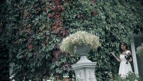 Retrato de una mujer joven atractiva en la situación blanca del vestido en jardín o parque metrajes