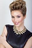 retrato de una mujer joven atractiva feliz hermosa que sonríe en un vestido de noche negro con el pelo y maquillaje con joyería c Foto de archivo libre de regalías