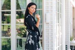Retrato de una mujer joven atractiva linda en la ropa de seda que sostiene sus propios vidrios en su mano El principiante hermoso imagenes de archivo