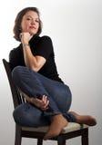 Retrato de una mujer joven atractiva que se sienta en una silla Fotografía de archivo libre de regalías