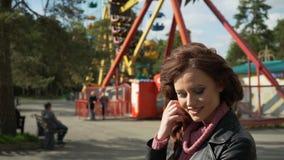 Retrato de una mujer joven atractiva que sonríe a la cámara con un carrusel en el fondo metrajes
