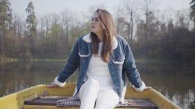 Retrato de una mujer joven bonita encantadora en vidrios y de una chaqueta del dril de algodón que flota en un barco en un lago o almacen de metraje de vídeo